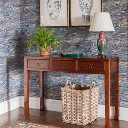 Foyer features an vintage Karaje area rug and lacquered console
