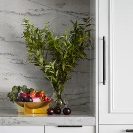 Custom white kitchen with full height quartzite backsplash