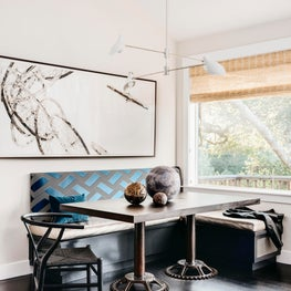 Bright, contemporary breakfast nook with blue banquette accents and industrial table