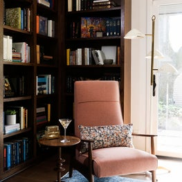 Mid-century modern study room with salamander color reupholstered chair and white floor lamp