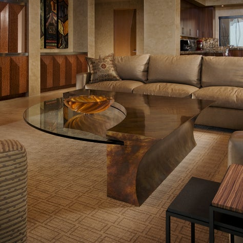 Award-winning patinaed bronze coffee table with cantilevered glass top.