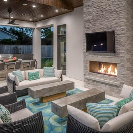 Cozy and stylish outdoor kitchen and living area complete with fireplace