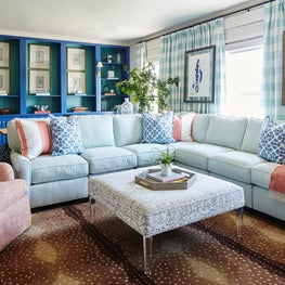 Family room with cobalt blue and turquoise cabinetry and a light blue sectional.