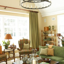 This transitional green & pale yellow room features a large eclectic chandelier.