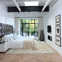 Bedroom with new chevron flooring and exposed beams.