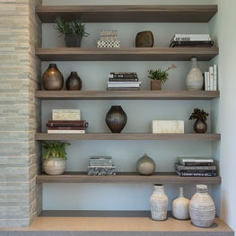 Modern bookcase styling next to textured fireplace wall, floating bench seat.