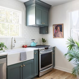 Cottage kitchen with green cabinets and a white apron farmhouse sink