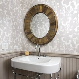 Whimsy powder room with a wood frame mirror.