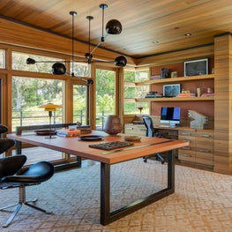 Modern home office with wood finishes, leather chair, and black globe chandelier