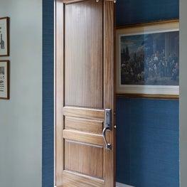 Entry foyer with peacock blue grasscloth, herringbone tile & wood door