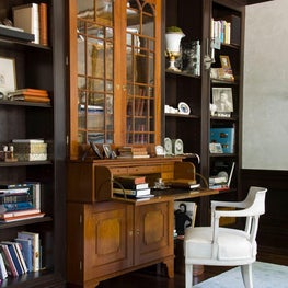 The home office maintains a masculine feel with wood paneling and chocolate colored walls.