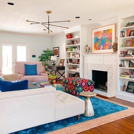 Family room with built in shelving and layered rugs