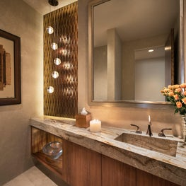 Warm amber glass border adds glamor to powder room