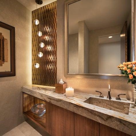 Warm amber glass border adds glamor to powder room