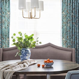 A Dining Area in an eat-in kitchen is complete with a custom banquette, drapery and an elegant light fixture.