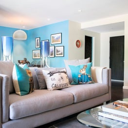 Modern Hollywood living room clad in neutral palette with bold blue accents