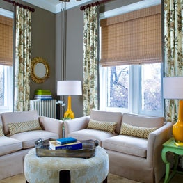 Cozy TV/Sitting Room with large floral print fabric and woven wood shades.