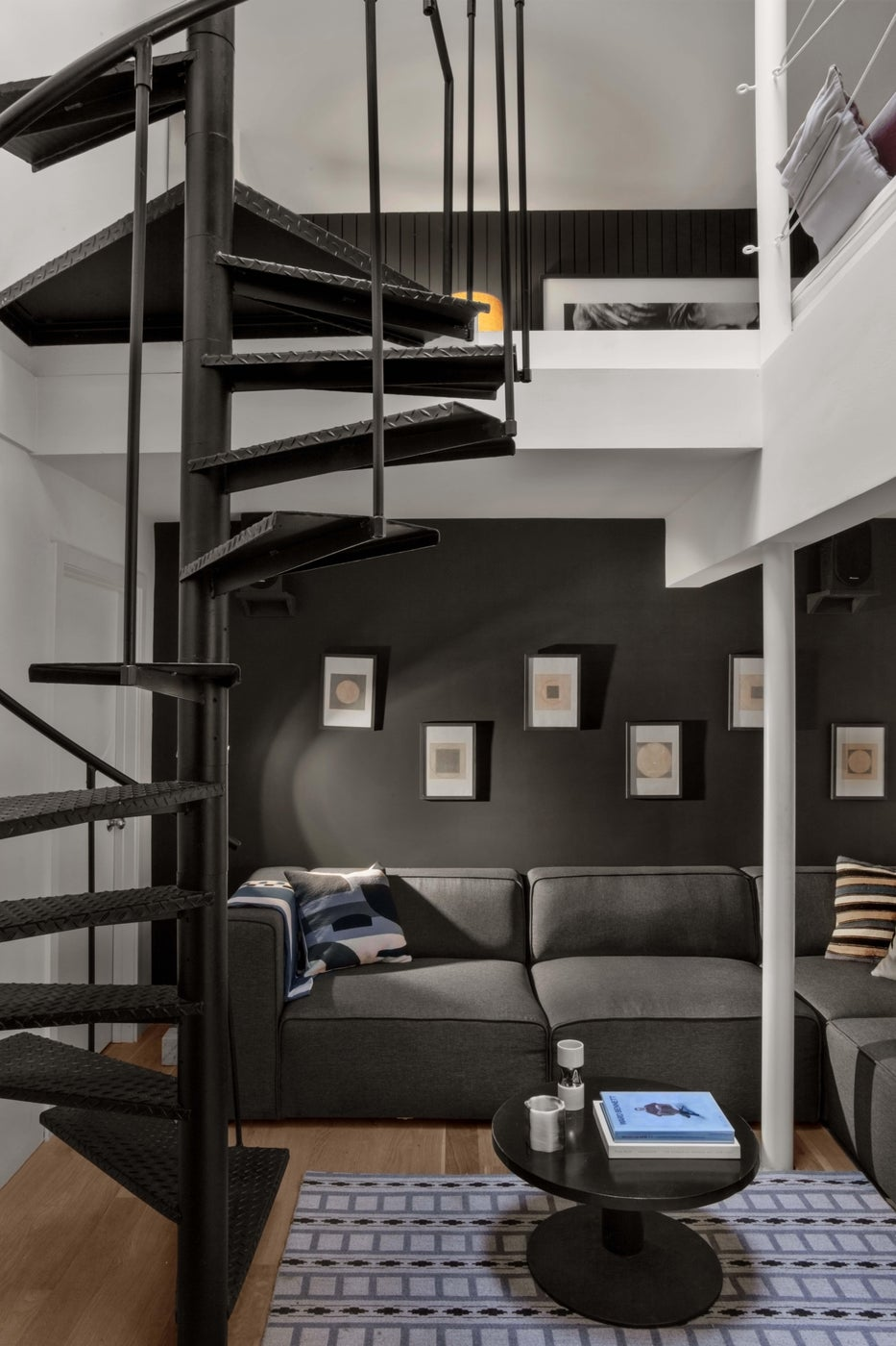 Grey & white modern lounge with spiral staircase, large sale art