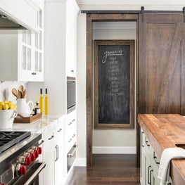 A barn-style pantry door in the kitchen and clever framed chalkboard for lists.
