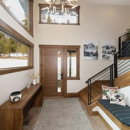Front door entry, wood console, custom bench cushion, metal stair railing, long rug and large chandelier