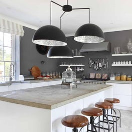 Open plan white kitchen in a converted stable featuring concrete top