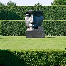 Layers of trimmed hedges frame sculpture and contrast with its sensuous forms.