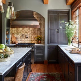 A blend of Italian and Craftsman styles, this kitchen with a custom copper hood and terra-cotta tiles creates a welcoming family space.