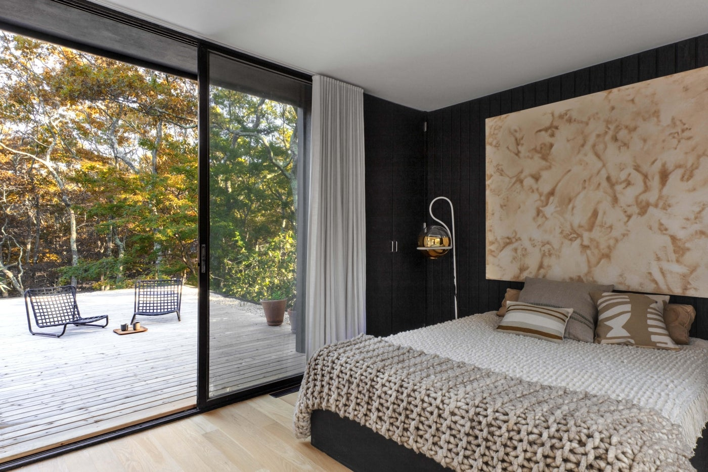 Modern bedroom with warm accents, glass wall overlooking outdoor patio