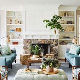 Blue and white coastal living room with stone fireplace and patterned textiles