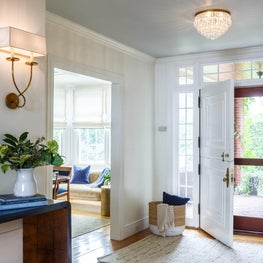 Foyer with brass sconces, zebra hide bench - interior design by Sophia Shibles