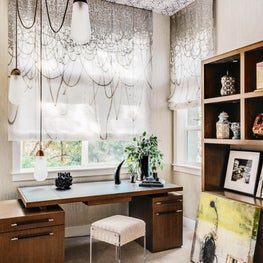 Home office with wallpapered ceiling, graphic shades, and contemporary wood desk