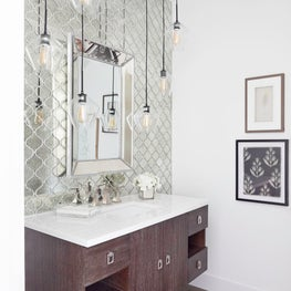 Geometric wall mirror with modern whimsical ceiling fixtures.
