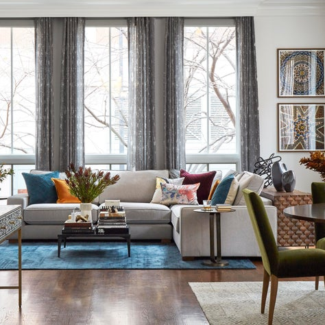 Great room with dark hardwood, floor to ceiling windows, sheer window drapery, colorful accents, blue, orange, red, wine, teal, camel, rust, green, walnut wood, brass accents, sectional sofa