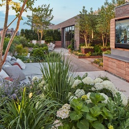 Outdoor TV, daybed and dining areas on lushly-planted rooftop terrace