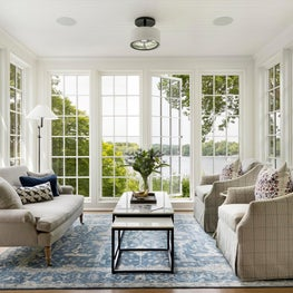 Sunroom wrapped in floor to ceiling windows.