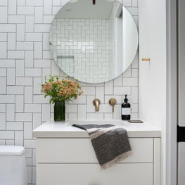 Bright, white bath with geometric tiled wall, round mirror, and leather-handled vanity