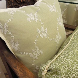 Spring green linen with lace overlay, and brocade pillows with elegant details.