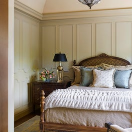 A guest bedroom with curved walls and french paneled wainscot