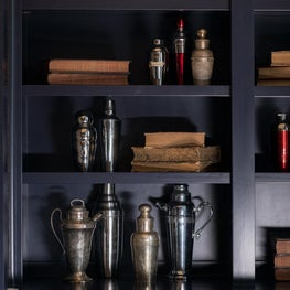 Collection of antique cocktail shakers adorn built-in cabinets