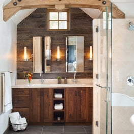 Mountain modern bath with light wood ceiling beams, glass shower & wood vanity.