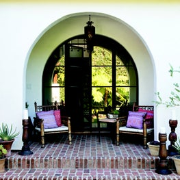 Arched steel and glass door with brick steps on a Spanish home