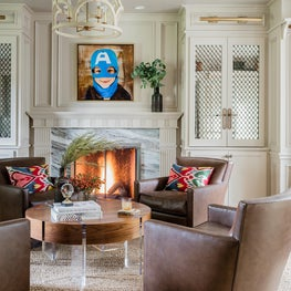 Cozy transitional living room library with fireplace and leather swivel chairs