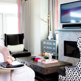 Sitting room with white couch, patterned chair, and tiled fireplace