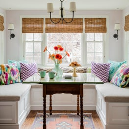 Bright and cheerful breakfast nook banquette colorful pillows antique table