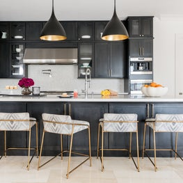 High contrast kitchen with dark stained cabinetry, white counters, and gold accents