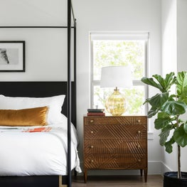 Scandinavian modern master bedroom with canopy bed and vintage rug