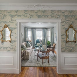 Wallpapered foyer with view into blue and white living room mirrors trim molding