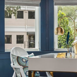 Contemporary gold and white lacquer desk w/ eclectic sculptural art & blue walls