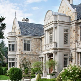 See how the bones of the exterior utilize stone and architectural detaling to personalize a historically inspired design, creating a handsome sillouette.
