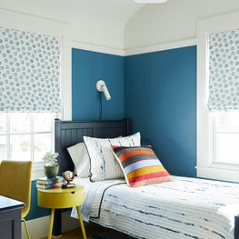 Boys bedroom with patterned window coverings and cool blue tone color scheme